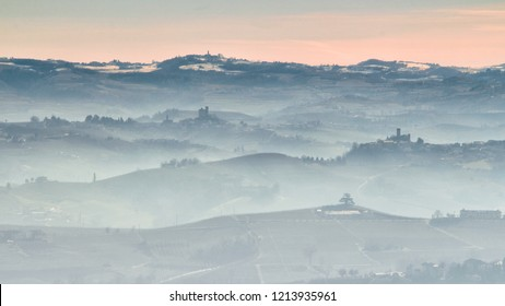 View of Langhe hills with vineyards in a foggy day from Verduno, Barolo area, Piedmont, Italy.