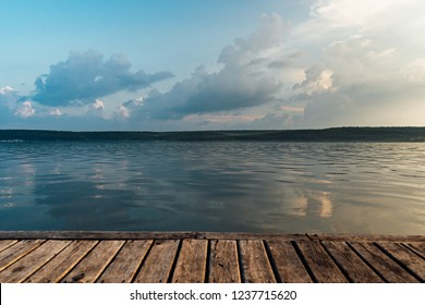 view of a large calm lake at sunset from a wooden pier