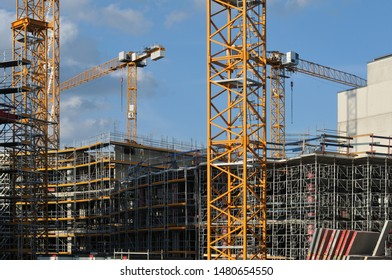 view to large construction site in a city with cranes and scaffolds at buildings