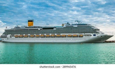 A view of a large cruise ship docked along the waterfront of Katakolon, Grece