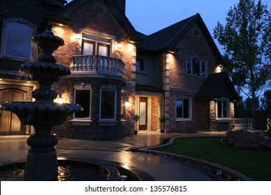view of a large luxurious home in the evening after a light rain with a fountain in the front