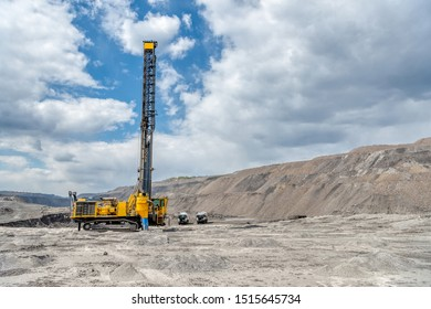 View of a large quarry for the extraction of limestone and coal. In the foreground is a field with drilled wells for blasting.