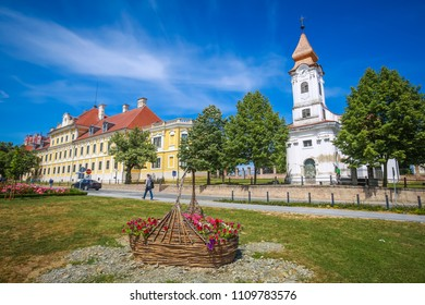 View of a large straw basket with flowers in a park with people walking in the street and the City museum and Chapel of the Saint Roko in the background in Vukovar, Croatia.