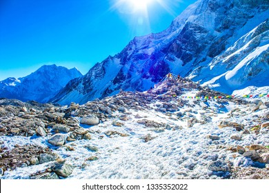 The view from the Larke Pass 5106 meters high peak at the Manaslu trekking path, Himalayas mountains, Nepal. Wind blowing prayers flags, snow, frozen ground and iced mountain peaks at the background.