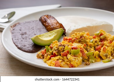 A view of a Latin American breakfast plate in a restaurant or kitchen setting.
