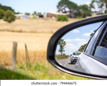 View from the left side rear view mirror of a car driving in a rural road with dry grass and farm fence on side. Cars following behind on a country road in remote area on a hot summer day.