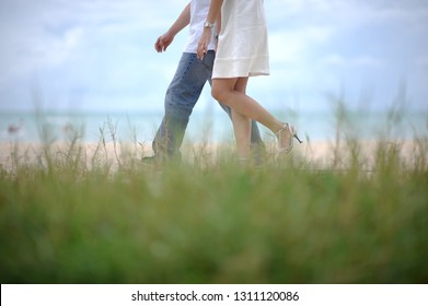 View of the legs of a loving couple walking by the seaside with grass in the foreground