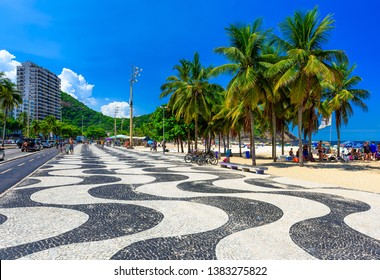 View of Leme beach and Copacabana beach with palms and mosaic of sidewalk in Rio de Janeiro, Brazil. Copacabana beach is the most famous beach in Rio de Janeiro. Sunny cityscape of Rio de Janeiro