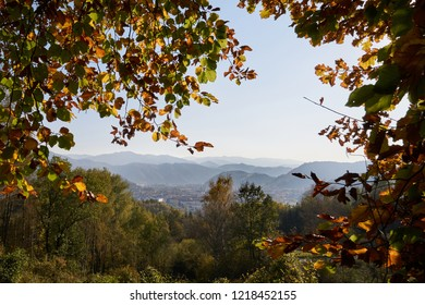 View from Leoben-Seegraben in Styria, Austria, to the autumnal landscape of Upper Styria, framed by colorful autumn leaves on a late afternoon in autumn