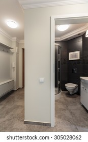 View of light corridor and bathroom with black walls