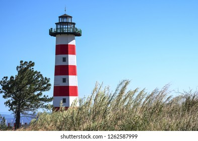 View of a light house with tall grass in front and a byue sku