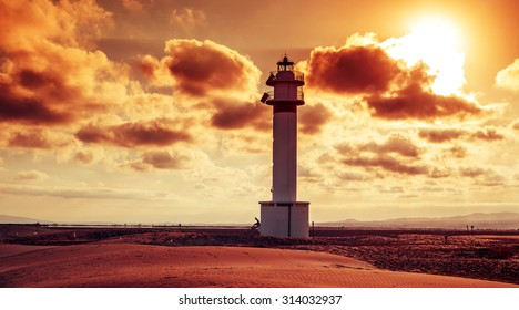 a view of the lighthouse at El Fangar, in the Ebro Delta, in Spain, at sunset in a cloudy day