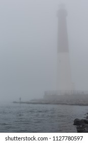 View of lighthouse with fisherman on a foggy morning