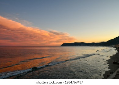 View of the Ligurian coast at sunset from the beach of Alassio with Capo Mele cape on the horizon