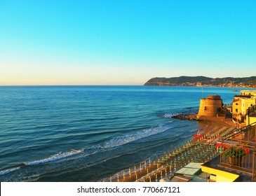 View of the Ligurian Sea, the beach in Alassio (province of Savona) at sunset, the Saracen Tower on the Italian Riviera in Western Liguria, Italy