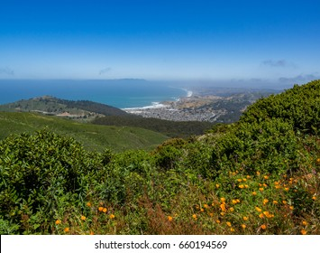 View of Linda Mar, California,  and Pacifica Beach with Pacific Ocean in the distance with poppies and chaparral.  Mount Tamalpais.  Seen from trail to Montara Peak, McNee Ranch State Park