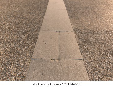 View of a line of light grey pavements on a granular dark grey background.