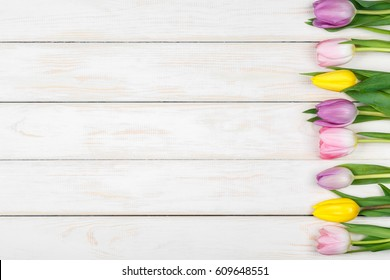 View of line of pink and yellow tulips lying on a white wooden background