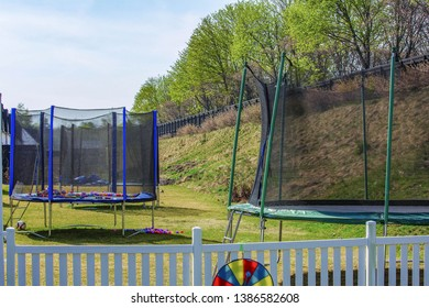 View of line of trampolines with saftey net mounted on backyards. Activity concept.