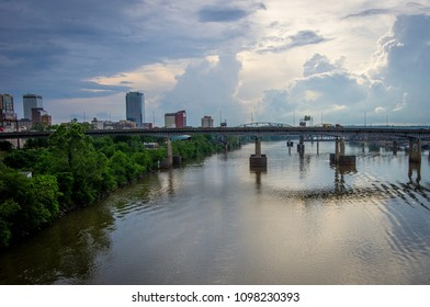 View of Little Rock bridges crossing the Arkansas river with the downtown skyline behind them.