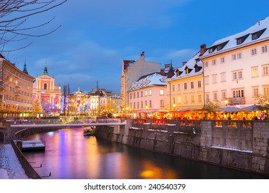 View of lively river Ljubljanica bank and Tromostovje in old city center decorated with Christmas lights at dusk. Ljubljana, Slovenia, Europe.