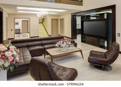 View of  living room with brown leather armchair, sofa and place for TV set. Glasses table of center of room and flowers in vase in table. Lighting room with brown, beige colors.