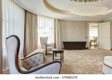 View of living room with two armchairs and rounded wooden table between. Interior of lighting room in beige and white colors. Big windows and luxury curtains.