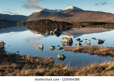 View of the Loch Etive with rocks on the foreground and a mountain range partially covered by snow reflected on the mirror-like lake's water, in Glen Etive, Highlands of Scotland, UK