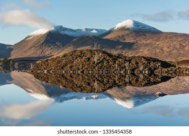 View of the Loch Etive under a blue sky where a mountain range partially covered by snow reflected on the mirror-like lake's water, in Glen Etive, Highlands of Scotland, UK
