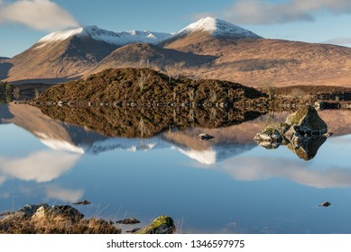 View of Loch Etive under a blue sky where a mountain range partially covered by snow reflected on the mirror-like lake's water, in Glen Etive, Highlands of Scotland, UK