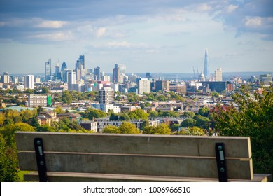 View of London city skyline from Parliament Hill in Hampstead Heath through an empty bench