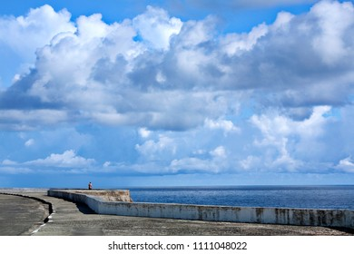 View of lonely man at distance on shabby embankment with white clouds in sky and blue sea water, Cuba