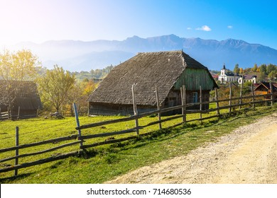 View at a lonely wooden house on slope meadow in Carpathian mountains in autumn. Orange foliage on trees. Blue mountain background with morning sun. Autumn landscape. Transylvania, Romania, Europe
