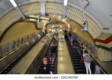View to a long escalator with passengers in a London subway station - London, UK - 08/02/2015