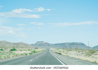 view of a long road leading to ridges in distance. straight highway along land with short plants ascends slightly to hills afar.