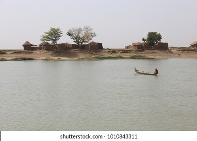 View of a long wooden typical pirogue with an african man and a child. The canoe is crossing the logone river to join the other side.  Picture taken at Kareska village in Chad on 2nd february 2017.