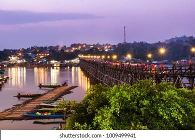 View of longest wooden Mon Bridge (saphan mon,Uttama Nusorn ) at Sangklaburi Kanchanaburi, Thailand at Sunrise. Beautiful violet sky with Mon Village.