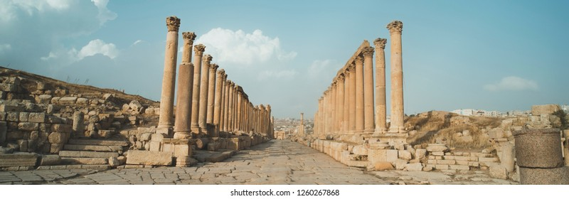 A view looking down the Cardo showing stone carved columns and paved street at the ancient city of Jarash or Gerasa, Jerash in Jordan. ancient Roman sights. Panorama
