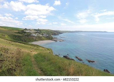 A view looking east from the coast path between Looe in Cornwall and Plymouth in Devon, towards Portwrinkle and its harbour, Whitsand bay and the Rame head peninsular