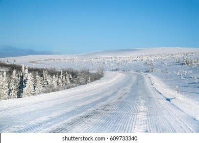 view looking north along Arctic Alaska's snow-covered Dalton Highway on blue sky day in late winter