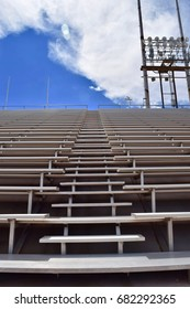 View looking up stadium bleachers with blue sky and clouds