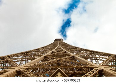 View looking up the wrought iron lattice framework from directly below of the iconic Eiffel Tower, Paris towards a cloudy sky
