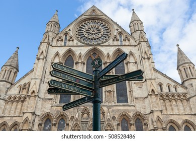 A view looking up at York Minster with a sign post, York, England.