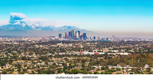 View of Los Angeles with smoke from a forest fire rising from the mountains behind