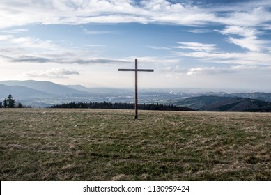 view  from Loucka hill with wooden cross on the summit and meadow in autumn Slezske Beskydy mountains in Czech republic
