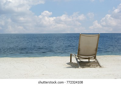 View of a lounge chair on a beach with the ocean in the background.
