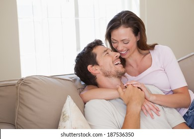 View of a loving young couple sitting on couch at home