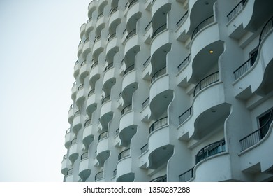 view from low angle on repeatedly geometric curve pattern exterior white wall or facade, balcony and window of an old vintage hotel in Penang. Malaysia.