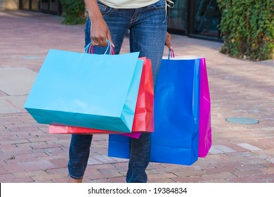 A view of the lower half of a person walking on a sidewalk in the city carrying colorful shopping bags.