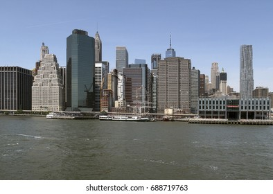 view of lower Manhattan, New York, along the East River, with the South Street Seaport and sightseeing boats in the foreground, June 26, 2017